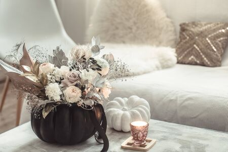 Home decor. Beautiful composition with fresh flowers in the interior of the room. The concept of coziness and comfort