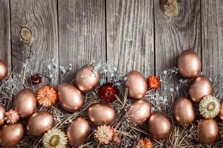 Golden Easter eggs on wooden background. The concept of the Easter holiday.