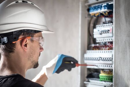 Man, an electrical technician working in a switchboard with fuses. Installation and connection of electrical equipment. Professional with tools in hand. concept of complex work