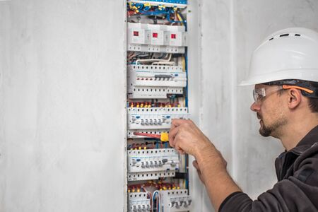 an electrical technician working in a switchboard with fuses.  Professional with tools in hand. concept of complex work, space for text.