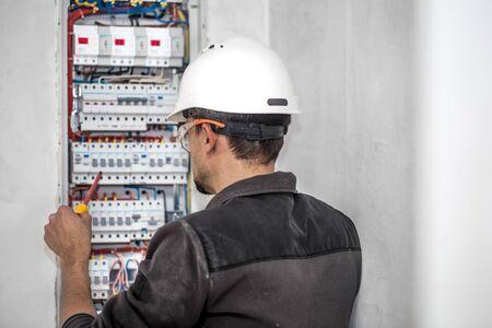 ein Elektrotechniker, der in einer Schalttafel mit Sicherungen arbeitet. Installation und Anschluss von elektrischen Geräten. Profi mit Werkzeugen in der Hand. Konzept der komplexen Arbeit, Platz für Text.