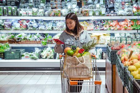 Une jeune femme fait ses courses dans un supermarché avec un téléphone dans les mains. Nourriture saine.