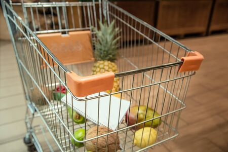 Trolley with food fruits and Notepad in the supermarket . Health food. Healthy food, organic food. Archivio Fotografico