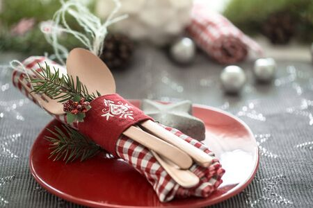 Beautiful serving of Cutlery on a red plate with decorative items on the Christmas table. The concept of the celebration . 스톡 콘텐츠