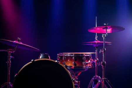 Drums and drum set. Beautiful blue and red background, with rays of light. Beautiful special effects of smoke and lighting. Musical instrument. The concept of music. Close-up photo. Stockfoto