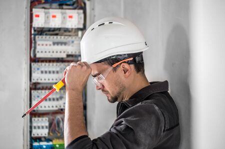 L'uomo, un tecnico elettrico che lavora in un quadro elettrico con fusibili. Installazione e collegamento di apparecchiature elettriche. Professionista con strumenti alla mano. concetto di lavoro complesso, spazio per il testo.