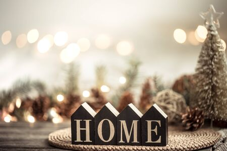 Festive background with lights and the inscription home on a wooden table. With festive decor items. The concept of Holiday and home comfort. Stock Photo