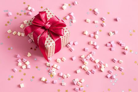 The concept of Valentine's day. Gift box with red bow on pink background. Marshmallows in the shape of a heart. Flat fly