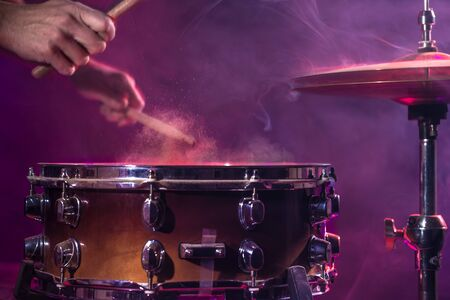 The drummer plays the drums. Beautiful blue and red background, with rays of light. Beautiful special effects smoke and lighting. The process of playing a musical instrument. The concept of music. Stock Photo