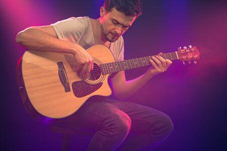 El músico toca una guitarra acústica. Hermoso fondo con rayos de luz de colores. El concepto de música y tocar un instrumento musical.