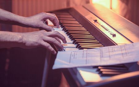 man plays the notes on the piano, close-up, beautiful color background, the concept of musical activity Archivio Fotografico