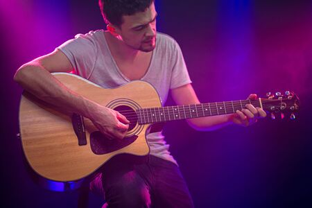 The musician plays an acoustic guitar. Beautiful background with colored light rays. The concept of music and playing a musical instrument.