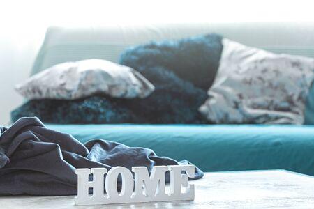 Bodegón en tonos azules, con inscripción de madera para el hogar y elementos decorativos, en el living.