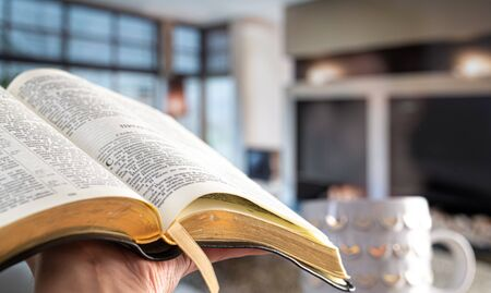 A man holds a Bible against the background of the living room. Reading a book in a cozy atmosphere. Close up.