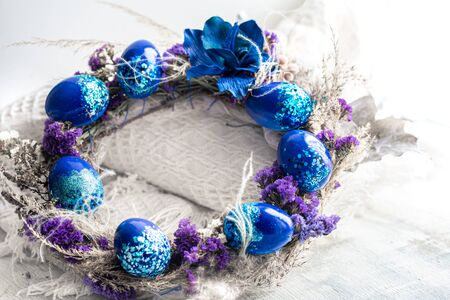 Easter wreath with blue eggs with sequins at the window . The concept of the Easter holidays and decor. Stock Photo - 137758962