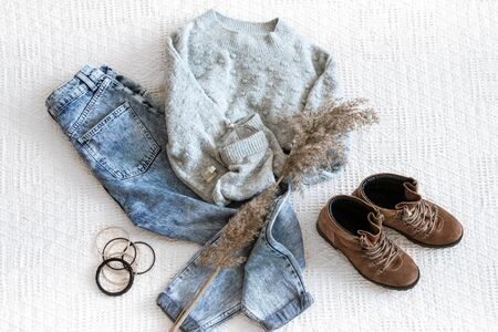 Set with fashionable women's clothing jeans and sweater, shoes and accessories . Top view, flat lay.