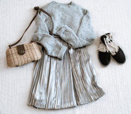 Ensemble avec jupe et pull à la mode pour femmes, sandales et accessoires. Vue de dessus, mise à plat.