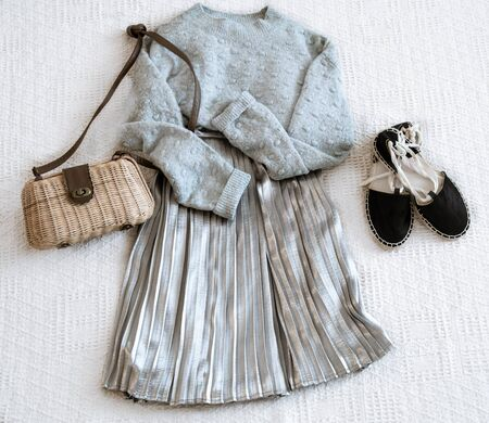 Set with fashionable women's clothing skirt and sweater, sandals and accessories . Top view, flat lay.