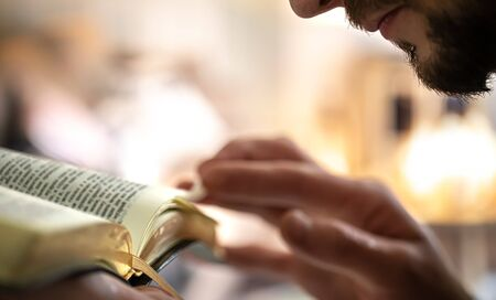 Man's hands over the Bible, against the background of the living room. Close up. Banco de Imagens