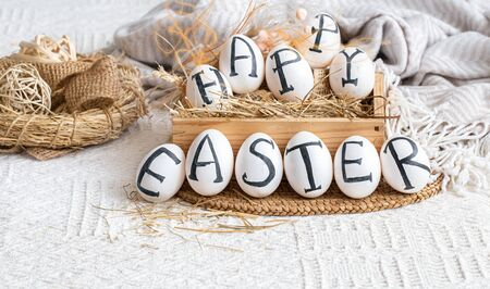 Easter eggs with the inscription happy Easter, holiday decor . Still life with an Easter cozy mood. Banco de Imagens