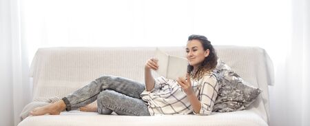 A woman is reading a book on a bright sofa in the room . The concept of hobby and education.