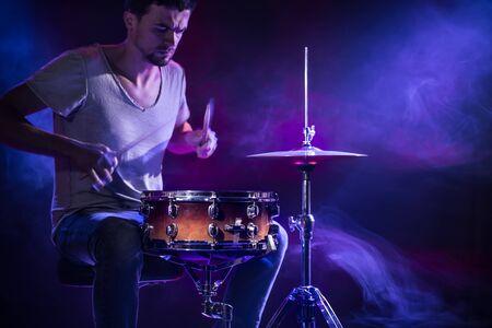 A drummer plays drums on a blue background. Beautiful special effects of light and smoke. The process of playing a musical instrument. The concept of music. Close-up photo.