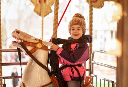 Little happy girl rides on a carousel, the concept of winter holidays.