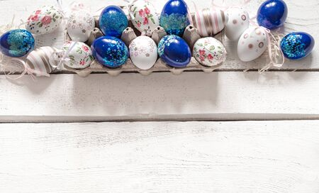 Stylish beautiful composition with blue Easter eggs on a white wooden background. The concept of Easter decorations and celebration.