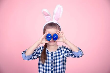 Portrait of a cute little girl with Easter eggs on an isolated pink background. Dressed in a blue plaid dress with a Hoop with Bunny ears. The concept of the Easter holidays. Banco de Imagens