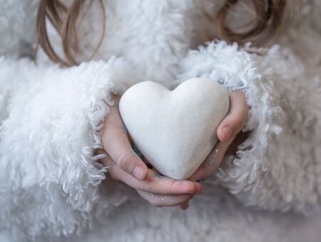 A little girl holds a white heart in her hands. Close up .