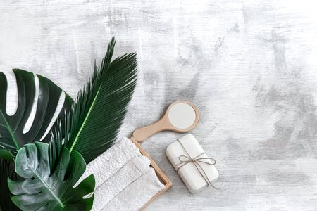 Spa. Body care items on a white background with tropical leaves. Summer accessories. Poster banner, postcard template. Space for text.