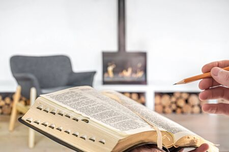 A man holding a Bible with a pencil, against the background of the living room with a fireplace. Reading a book in a cozy environment. Close up. Banco de Imagens