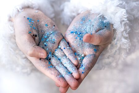 The hands of a little girl in blue sequins. Close up