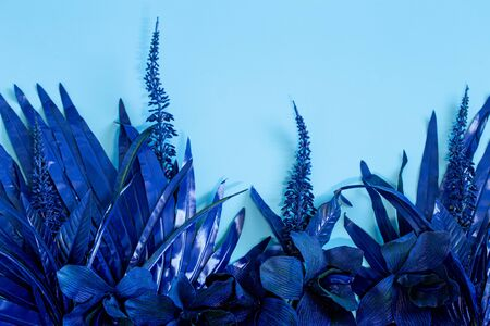 Artificial tropical beautiful blue Orchid flowers and leaves, background. Trending blue. Space for text.