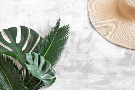 Tropical leaves on a white background with summer accessories Concept of summer vacation and recreation. Poster banner, postcard template. Space for text.