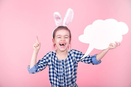 Easter Sale Banner. Easter portrait of a cute little girl with space for text, isolated pink background. Dressed in a blue plaid dress with a Hoop with Bunny ears. The concept of Easter holidays.