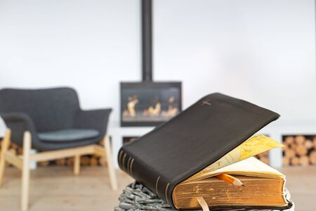 Bible book with pencil, on the background of the living room with a fireplace. Reading a book in a cozy environment. Close up. Banco de Imagens