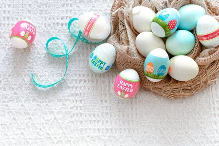 A nest of hay with beautiful Easter colored eggs on a light background. The concept of the Easter holidays.
