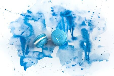 Dessert macaroon on a blue watercolor background, stylish creative background.