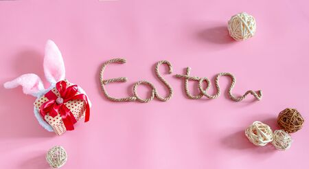 Spring Easter festive background. Creative inscription on a pink background with items of decor. The concept of the Easter holiday.