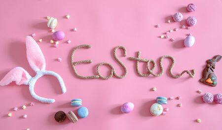 Spring Easter festive background. Creative inscription on a pink background with items of decor. The concept of the holiday.