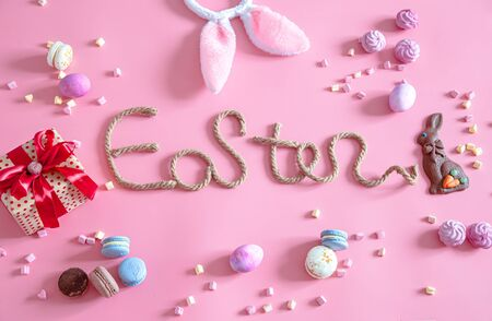 Spring Easter festive background. Ceative inscription on a pink background with items of decor. The concept of the holiday.