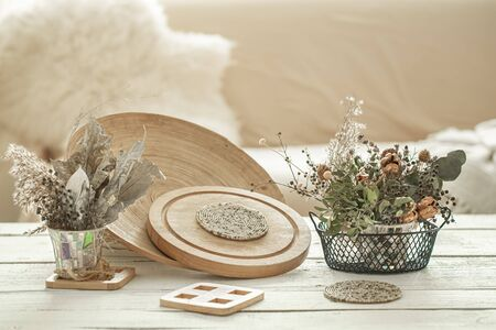 Decorative items in the cozy interior of the room , a vase with dried flowers on a light wooden table.