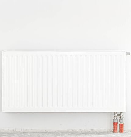 Radiator in front of a white wall. Front view. Space for text.