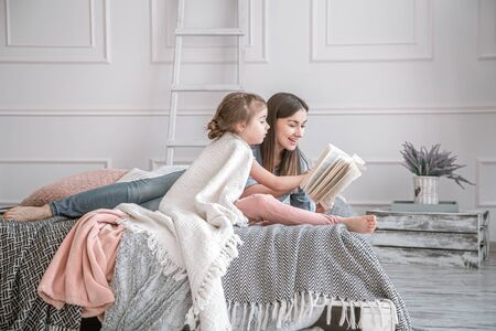 Portrait of a smiling young cute mother and daughter reading a book lying and relax in the bed in a bright big white room. Concept of children's education and development.