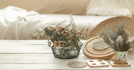 Decorative items in the cozy interior of the room , a vase with dried flowers on a light wooden table. 版權商用圖片