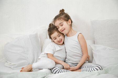 Two cute little sister girls are cuddling on the bed in the bedroom. The concept of family values and children's friendship.