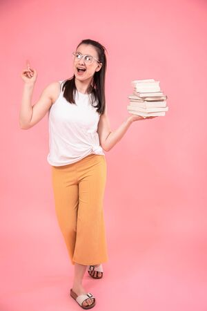 Portrait of a young woman with glasses on a pink background with books in her hands . Concept of education and Hobbies.