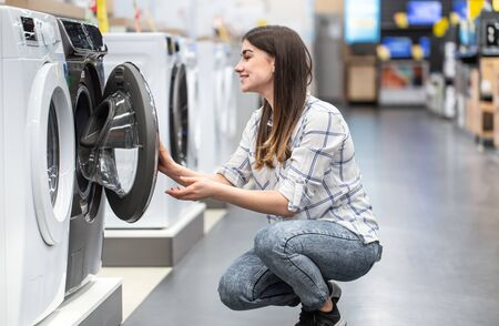 A young woman in a store chooses a washing machine.. The concept of shopping.