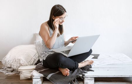 A young woman works remotely at a computer at home. Freelancer and work on the Internet.
